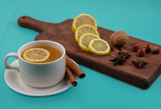 Вид сбоку чашки чая с ломтиком лимона и корицей на блюдце с орехами, нарезанным грецким орехом, лимоном на разделочной доске на синем фоне