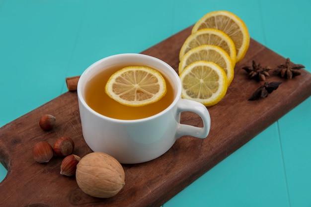 Вид сбоку чашки чая с ломтиками лимона и корицей с орехами грецким орехом на разделочной доске на синем фоне