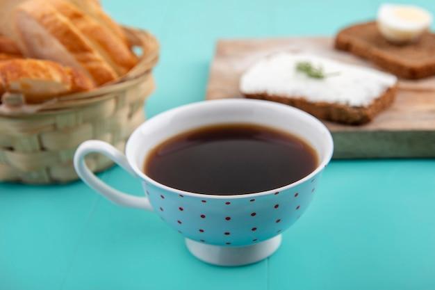 Вид сбоку на чашку чая с нарезанным багетом и ломтиками ржаного хлеба, намазанными сыром и яйцом с кусочком укропа на синем фоне