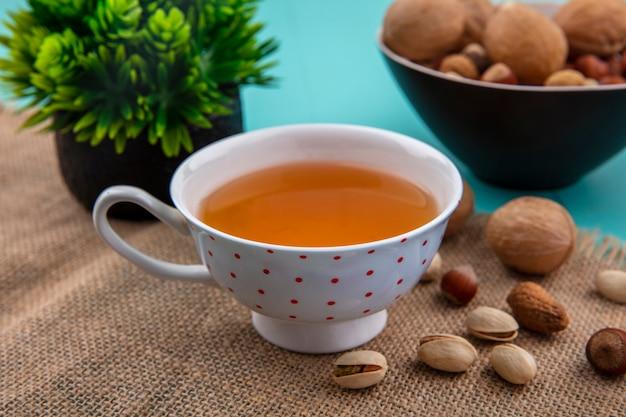 Вид сбоку на чашку чая с грецкими орехами, фундуками с фисташками и на бежевой салфетке