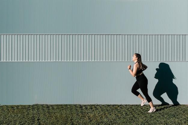 오후에 야외에서 실행하는 매력적인 젊은 운동 여자의 측면보기