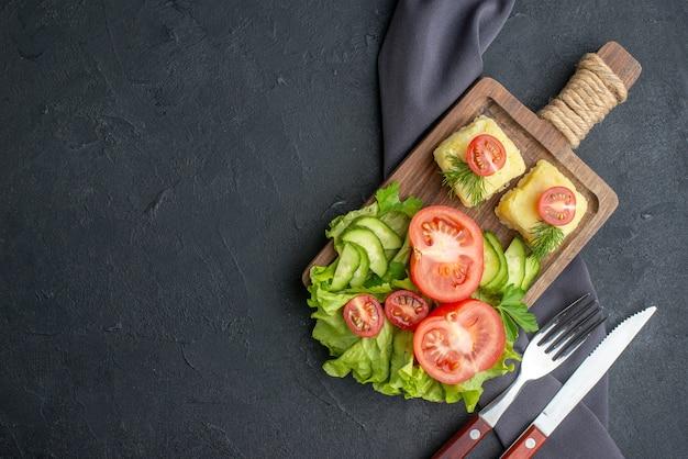 黒い表面の左側にある木の板にカットされたフレッシュトマトとキュウリのチーズの側面図