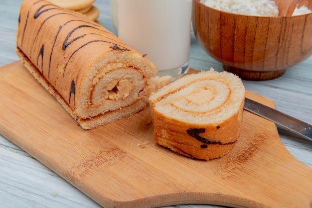 Вид сбоку нарезанного рулета и рулет с ножом на разделочную доску и молоко творожное печенье на деревянный стол