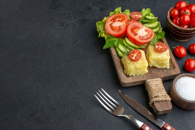 Вид сбоку нарезанных целых свежих помидоров и огурцов, сыра на деревянной доске, набор столовых приборов, соль с левой стороны на черной поверхности