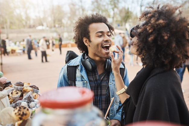 フードフェスティバルの間に公園で楽しんで、カウンターの近くに立って、何か食べるものを選んで恋にかわいいアフリカ系アメリカ人カップルの側面図。