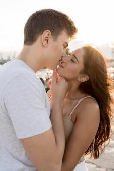 Вид сбоку милая пара, целующаяся на открытом воздухе
