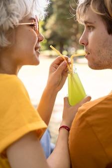 公園のストローでジュースを共有するかわいいカップルの側面図