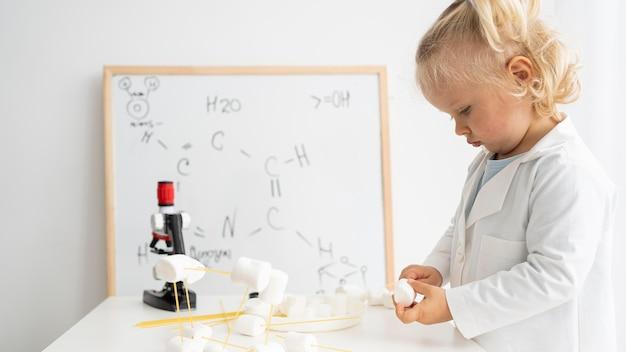 화이트 보드와 현미경으로 과학에 대해 배우는 귀여운 유아의 측면보기