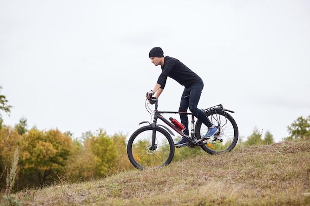 ダウンヒルマウンテンバイクに乗ってサイクリスト、屋外の自転車でエクストリームスポーツ、黒いスポーツスーツと帽子を着ている若いスポーツマンの側面図
