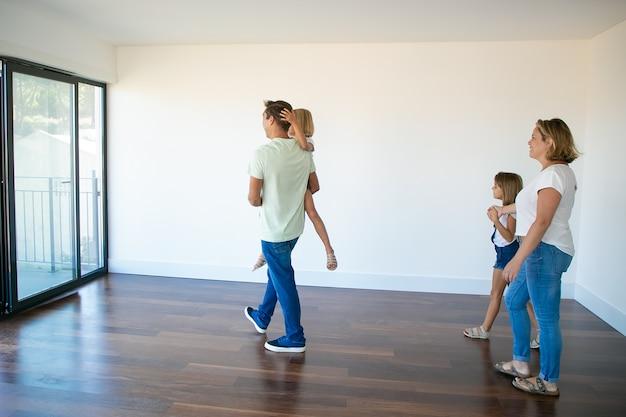 Вид сбоку на папа, держащего дочь и идущего с ней на балкон