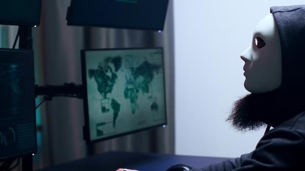 흰색 마스크를 쓴 위험한 사이버 범죄자의 측면. 위험한 바이러스.