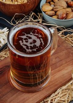 Вид сбоку темного пива в кружку на деревянной доске с соломой на деревенском