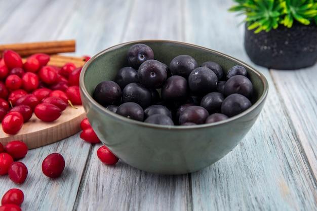회색 나무 배경에 계피 스틱 나무 주방 보드에 빨간 산딸 나무 열매와 그릇에 어두운 피부 인목 무리의 측면보기