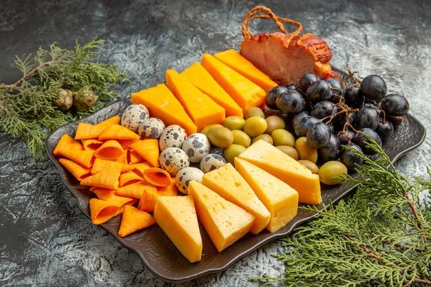 Вид сбоку вкусной лучшей закуски для вина на коричневом подносе и еловых ветках на фоне льда