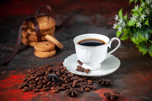 Вид сбоку на вкусный кофе в белой чашке и жареные бобы уложенный печеньем цветок на смешанном цветном фоне со свободным пространством