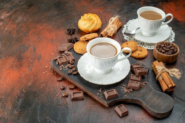 Вид сбоку вкусного кофе в белых чашках на деревянной разделочной доске, печенье, корица, лайм, шоколадные батончики с левой стороны на смешанном цветном фоне