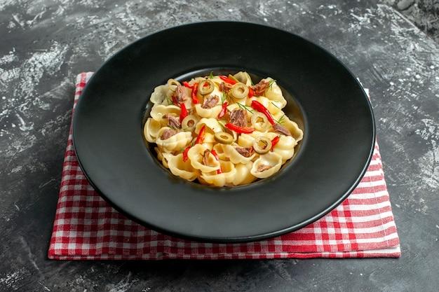 皿に野菜と緑、灰色の背景に赤いストリップタオルにナイフとおいしいコンキリエの側面図