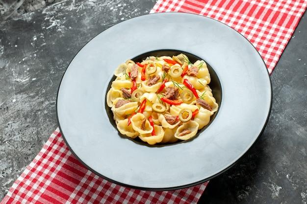 회색 배경에 빨간색 벗겨진 수건에 칼과 접시에 야채를 넣은 맛있는 콘치글리의 측면