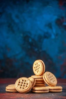 다양한 형태로 배열된 맛있는 쿠키의 측면과 여유 공간이 있는 혼합 색상 배경에 꽃