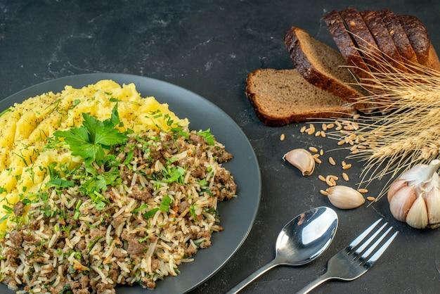 Вид сбоку вкусного ужина с мясом и картофельным пюре на серой тарелке, ломтики хлеба, набор столовых приборов с чесночным шипом на черном фоне