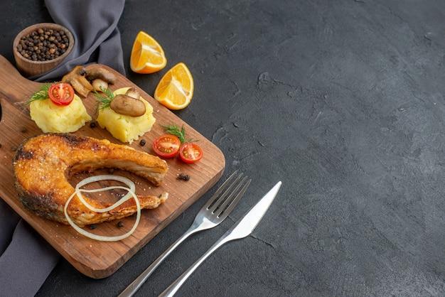 木の板にキノコ野菜チーズとおいしい揚げ魚料理の側面図黒の苦しめられた表面に設定された暗い色のタオルカトラリーにレモンスライスペッパー