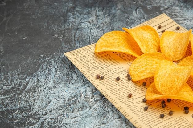 회색 테이블에 신문에 맛있는 수제 칩과 후추 그릇 마요네즈 케첩의 측면보기