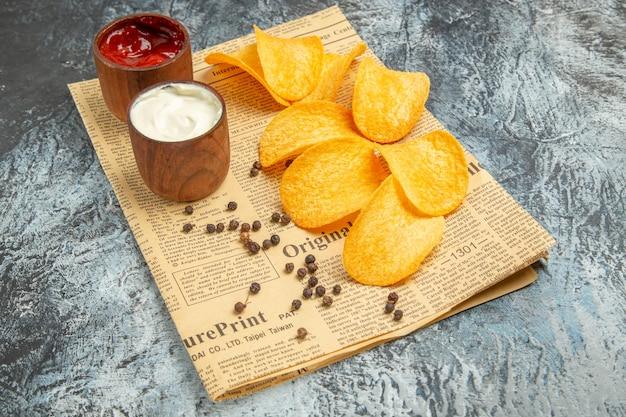 Вид сбоку вкусных домашних чипсов и майонезного кетчупа с перцем на газете на сером столе