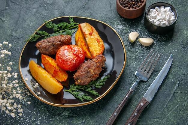 검은 접시에 감자와 토마토로 구운 맛있는 고기 커틀릿의 측면 보기 녹색 검정 혼합 색상 배경에 설정된 마늘 향신료 칼붙이