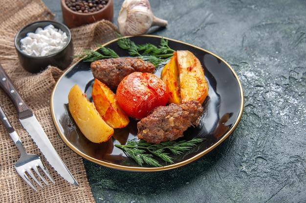 Вид сбоку вкусных мясных котлет, запеченных с картофелем и помидорами на черной тарелке, набор столовых приборов со специями и чесноком на зеленом черном фоне цветов