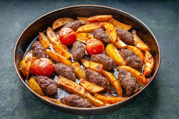 녹색 및 검은색 혼합 색상 배경에 감자와 토마토로 구운 맛있는 고기 커틀릿의 측면 보기