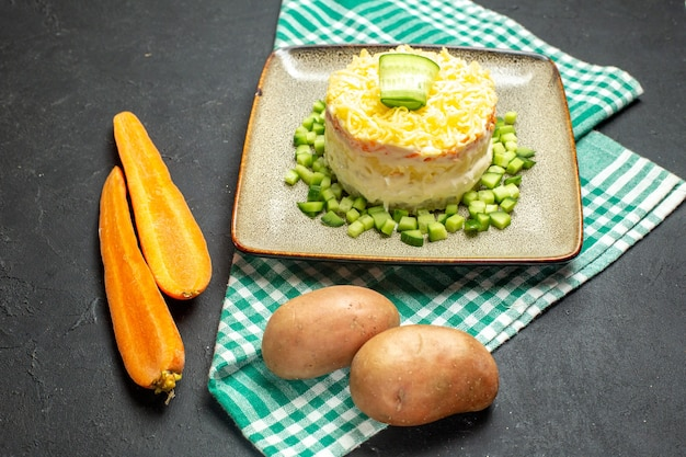 반으로 접힌 녹색 벗겨진 수건 당근과 어두운 배경에 감자에 다진 오이를 곁들인 맛있는 샐러드의 측면