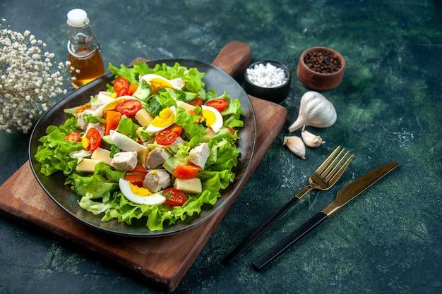 木製のまな板スパイスオイルボトルニンニクカトラリーに多くの新鮮な食材を使ったおいしいサラダの側面図をブラックグリーンミックスカラーの背景に設定