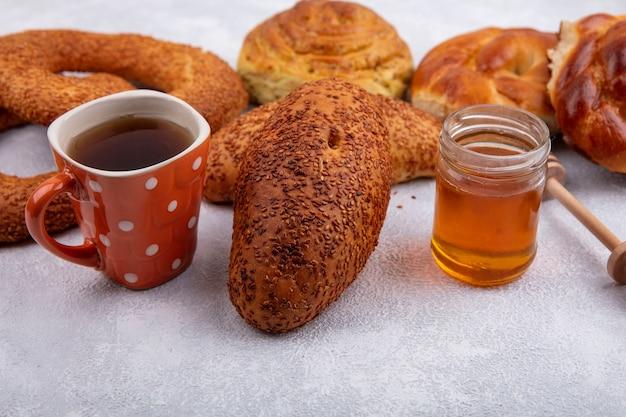 Вид сбоку вкусных кунжутных котлет с чашкой чая и медом на стеклянной банке и различными булочками, изолированными на белом фоне
