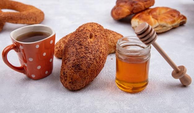 Вид сбоку вкусных кунжутных котлет с чашкой чая и медом на стеклянной банке на белом фоне