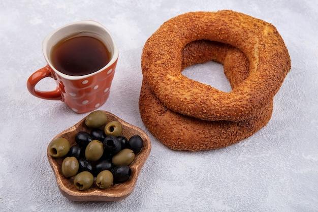 Вид сбоку вкусных кунжутных турецких рогаликов с чашкой чая и оливками на деревянной миске на белом фоне