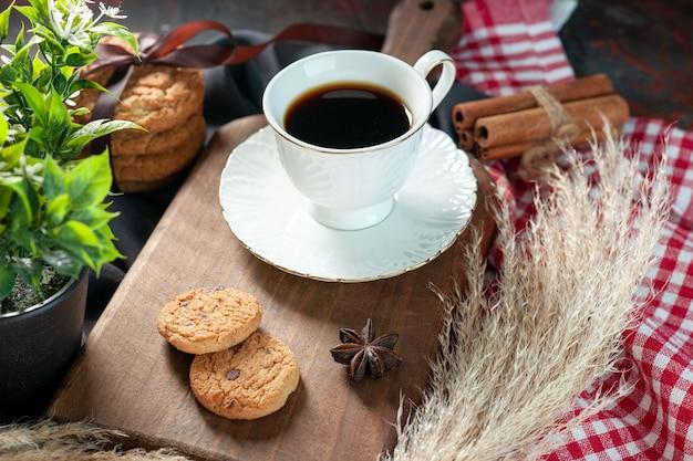 Вид сбоку на вкусное сложенное печенье, перевязанное лентой на деревянной доске, и чашка кофе на деревянной доске, шипы, полотенца, цветок, корица, лайм на фоне темных цветов