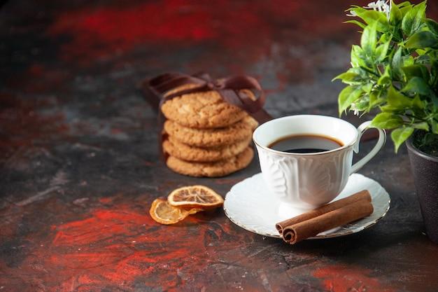 Вид сбоку на вкусное сахарное печенье и чашку кофейного цветочного горшка с корицей и лаймом на темном фоне цветов