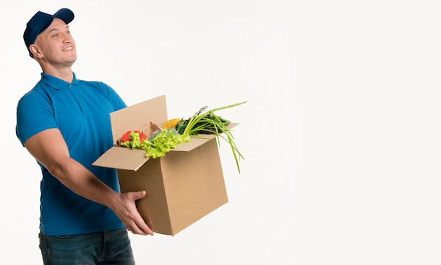 Вид сбоку доставщик держит коробку с продуктами