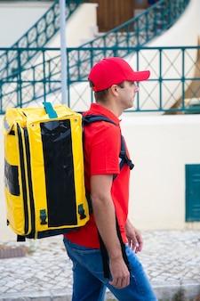 빨간 모자와 셔츠보고 필요한 집 배달원의 측면보기. 노란색 열 배낭이있는 진지한 택배가 도보로 빠른 주문을 전달합니다. 음식 배달 서비스 및 온라인 쇼핑 개념