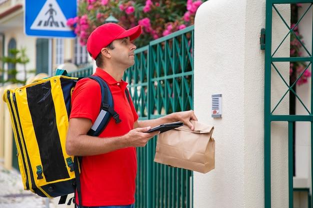入り口で顧客を待っている赤い帽子の配達員の側面図。黄色のサーマルバックパックとパケットを備えた本格的な宅配便で、クライアントにエクスプレスオーダーを提供します。配送サービスとポストコンセプト
