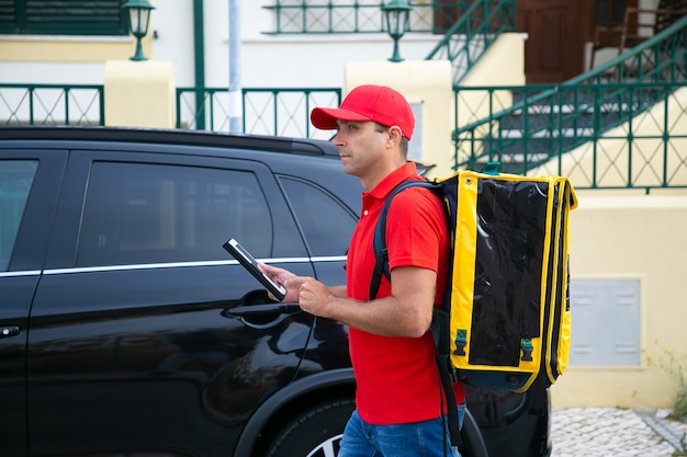 태블릿에 배달원보고 주소의 측면보기. 빨간 모자와 셔츠에 노란색 열 가방이있는 콘텐츠 택배가 도보로 빠른 주문을 전달합니다. 음식 배달 서비스 및 온라인 쇼핑 개념