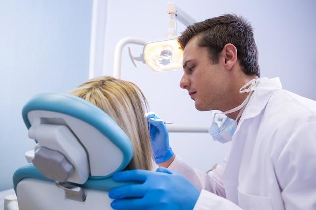 Вид сбоку стоматолога, полирующего зубы женщины