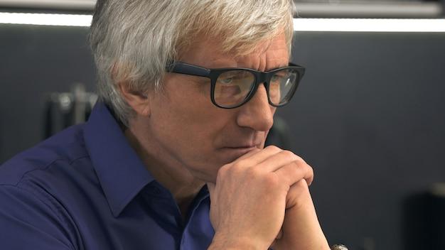 眼鏡をかけて落ち込んでいる年配の男性の側面図