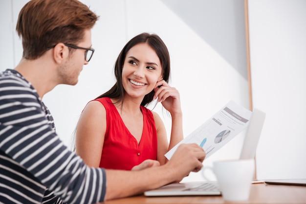 Вид сбоку диалога пары, сидящей за столом с ноутбуком и документами в офисе