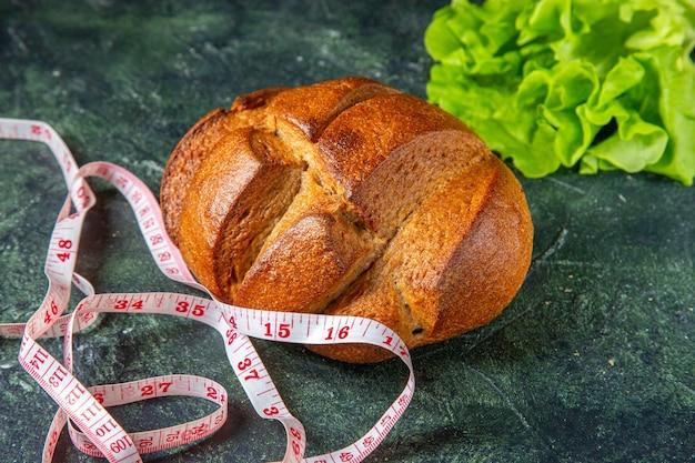 暗い色の表面に食事の黒いパンとメートルの緑の束の側面図