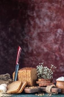 混合色の背景にボウル茶色のタオルで木製まな板ナイフ花卵粉の食餌療法の黒いパン小麦の側面図