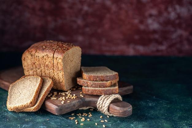 青い栗色の混合色の背景に木製まな板の上の食餌療法の黒いパン小麦の側面図