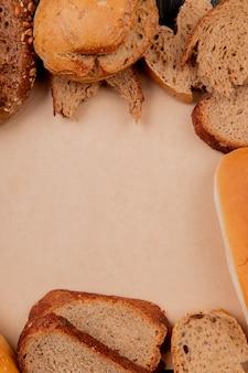 コピースペースを持つ段ボールの表面にライ麦黒バゲットサンドイッチのものとして別のパンの側面図