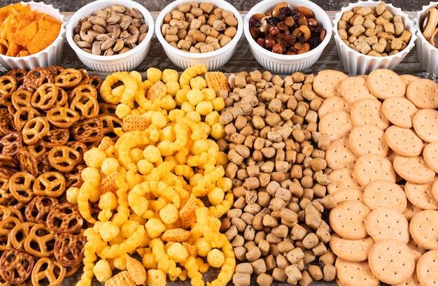 白い木製の表面の水平にナッツ、クラッカー、クッキーとしてスナックの異なる種類の側面図