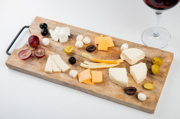 白のまな板の上のブドウの部分とオリーブとチーズの種類の側面図